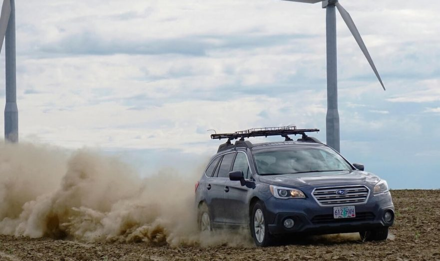 Subaru Outback drifting through dirt.